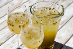 Passionfruit lemonade in glass pitcher. Passionfruit, passionfruit, maracuja lemonade. Fresh cold soda drink. Pitcher and two glasses made of glass. wood table Stock Images