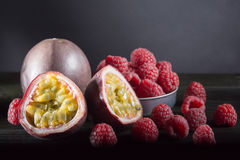 Passionfruit and many raspberries on black wooden table on dark. Background, moonlight, room for text Stock Photos
