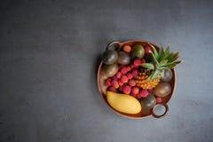 Passionfruit med ananas och mango på grå färgtabellen, bästa sikt Royaltyfri Fotografi