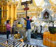 Passionnés bouddhistes baignant des statues de Bouddha à la pagoda de Shwedagon Photographie stock