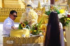 Passionnés bouddhistes baignant des statues de Bouddha à la pagoda de Shwedagon Images libres de droits