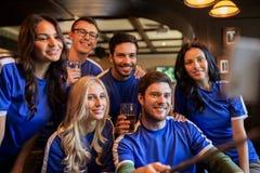 Passionés du football avec de la bière prenant le selfie au bar Images libres de droits