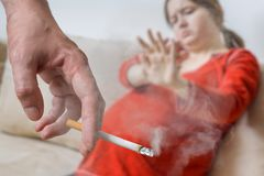 Passive smoking in pregnancy. Selfish man is smoking cigarette Royalty Free Stock Photo