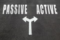 Passive vs active choice concept. Two direction arrows on asphal Stock Photography