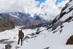 Passo di montagna diritto della neve dell'alpinista di viaggiatore con zaino e sacco a pelo sopra il ghiacciaio Fotografia Stock