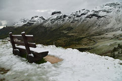 Passo Pordoi: bench covered by the first snow of the season Stock Photos