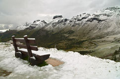Passo Pordoi: bench covered by the first snow of the season Stock Image