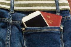 Passort ed il cellulare in tasca delle blue jeans significa il viaggio Fotografie Stock Libere da Diritti