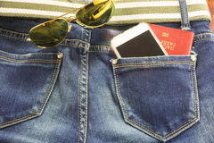 Passort and mobile in blue jeans pocket means  journey Royalty Free Stock Photography