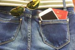 Passort y el móvil en bolsillo de los tejanos significa viaje Fotografía de archivo libre de regalías