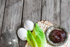 Passover background. Wine, egg, bitter salad leaves, matzot and haroset - traditional jewish passover celebration elements. Copy space background Royalty Free Stock Photos