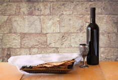 Passover background. wine and matzoh (jewish passover bread) on wooden table and wall texture from jerusalem stone Royalty Free Stock Photo