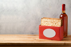 Passover celebration concept with matzoh and wine bottle on wooden table over bright background Royalty Free Stock Images