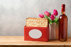 Passover celebration concept with wine bottle, matzoh and tulip flowers Stock Photo