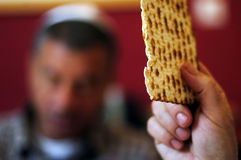 Passover Dinner Celebrations. A man is blessing on Matzah (unleavened bread) while another wearing a kippah (scullcap) reads the Haggadah (traditional text) Royalty Free Stock Images