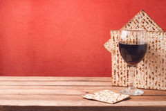 Passover holiday background with wine glass and matzoh on wooden table Stock Images