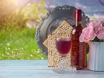 Passover holiday celebration concept. With wine, matzo, flowers and seder plate over green grass background Stock Photos