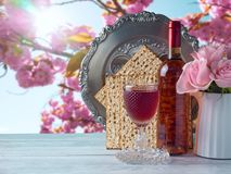 Passover holiday celebration concept. With wine, matzo, flowers and seder plate over spring background Royalty Free Stock Photos