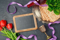 Passover holiday concept matzoh, chalkboard and tulip flowers on dark background. Royalty Free Stock Photography