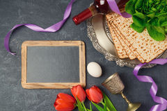 Passover holiday concept seder plate, matzoh and chalkboard on dark background. Top view from above Royalty Free Stock Image