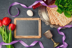 Passover holiday concept seder plate, matzoh and chalkboard on dark background. Top view. From above Royalty Free Stock Image