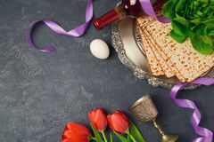 Passover holiday concept seder plate, matzoh and tulip flowers on dark background. Top view Stock Photos