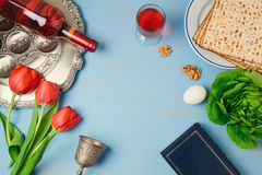 Passover holiday concept seder plate, matzoh, tulip flowers and wine bottle on wooden background. Stock Photo