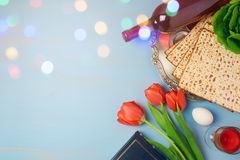 Passover holiday concept seder plate, matzoh and tulip flowers on wooden background with bokeh overlay. Top view Stock Images