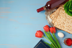 Passover holiday concept seder plate, matzoh and tulip flowers on wooden background. Stock Images
