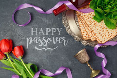 Passover holiday greeting card matzoh and tulip flowers on dark background. Top view Stock Photography