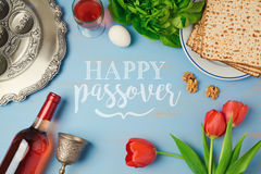 Passover holiday greeting card with seder plate, matzoh, tulip flowers and wine bottle on wooden background. Top view from above Stock Image