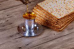 Passover matzo with kiddush cup wine on wooden table Royalty Free Stock Photo