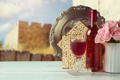 Passover matzo and wine. On wooden vintage table over old city walls. Seder plate with hebrew text says egg Stock Image