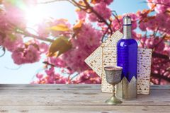 Passover matzo and wine. On wooden vintage table over spring flowers background Royalty Free Stock Photo
