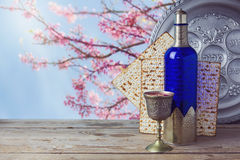 Passover matzo and wine on wooden vintage table over blossom tree background. Royalty Free Stock Photos