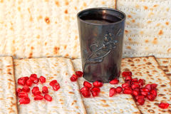 Passover. Matzoh (matzah or matzo) - Jewish traditional Passover (Pesach) holiday bread, pomegranat grains and silver glass with wine background Stock Image