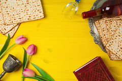 Passover Pesah celebration with matzoh, tulip flowers and wine bottle on yellow wooden background. Stock Photo