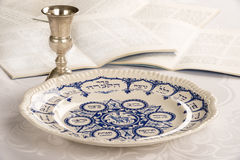 Passover Plate with Kiddush Cup and Haggadah. Passover Plate on white linen table cloth with Kiddush cup and Haggadah Stock Image