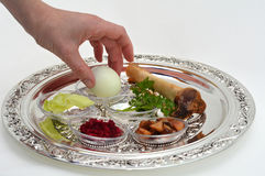 Passover Seder Plate. Jewish woman hand organizing Passover Seder Plate with The seventh symbolic item used during the seder meal on passover Jewish holiday Stock Photos