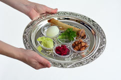Passover Seder Plate. Jewish woman hands carry Passover Seder Plate with The seventh symbolic item used during the seder meal on passover Jewish holiday.White Royalty Free Stock Image