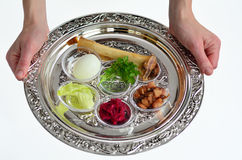 Passover Seder Plate. Jewish woman hands carry Passover Seder Plate with The seventh symbolic item used during the seder meal on passover Jewish holiday.White Royalty Free Stock Photo