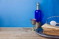 Passover tło z winem, matzoh i jajkiem nad błękit ścianą, zdjęcia stock