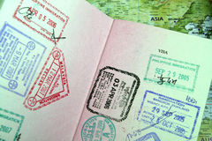 Passport with Asian Travel Stamps. Passport with various stamps of Asian destinations. Partial view of the map of Asia shown in the background stock photography