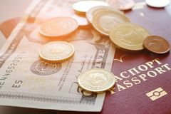 Passport with banknotes and coins on a plain background stock images
