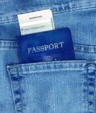 Passport and Boarding Pass in Pocket. Passport and boarding pass in back pocket of blue jeans Royalty Free Stock Image