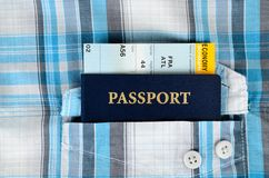 Passport,and boarding pass in a pocket of shirt. Passport,and boarding pass in a pocket of plaid shirt Royalty Free Stock Images