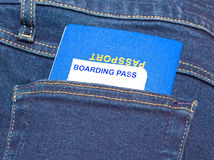 Passport and boarding pass sticking out of jeans pocket. Stock Photos