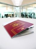 Passport and boarding pass, waiting for a flight in an airport Stock Photos