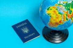 Passport of a citizen of Ukraine near the globe on a blue background stock photography