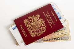 Passport with Currency. British Passport with foreign currency on a white backgrond royalty free stock photography
